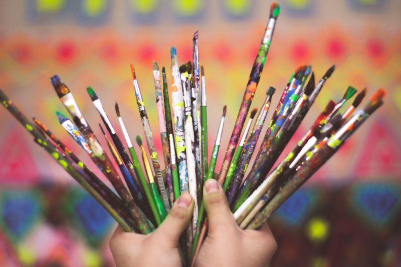 A pair of hands holding up several dozen paintbrushes against a colorful mural