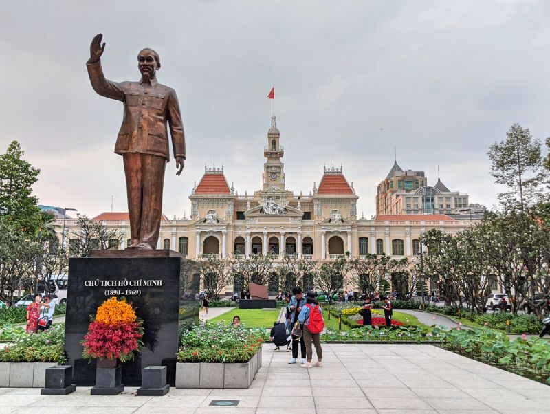 Ho Chi Minh bronze statue with a beige French style building in the backdrop