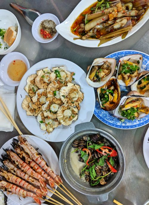 A table filled with a variety of seafood such as grilled prawns, shellfish, scallops, and oysters at Oc Dao in Ho Chi Minh City, Vietnam