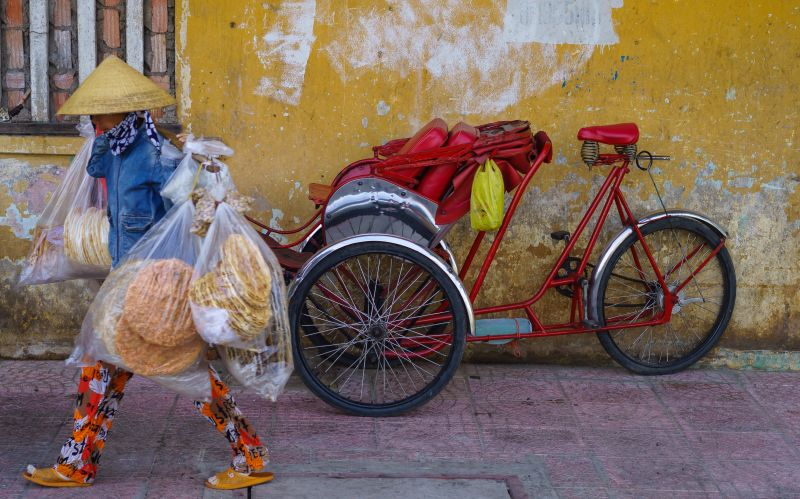 A person wearing a conical hat and selling rice crackers pass by a red cyclo in Ho Chi Minh City, Vietnam