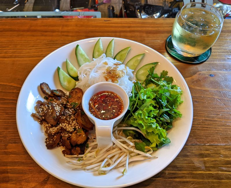 A Vietnamese vegetarian dish with faux meat, rice noodles, lettuce, bean sprouts, and vegan fish sauce.