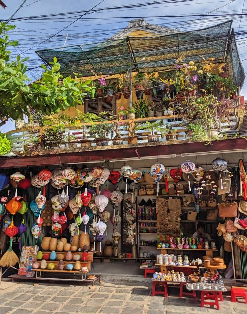 A store in Hoi An Ancient Town selling souvenirs such as silk lanterns, handbags, ceramic pots, and more.