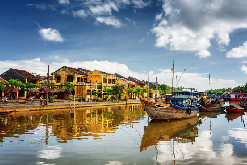 Hoi An, Vietnam is a charming city with yellow buildings and a river that has boats.