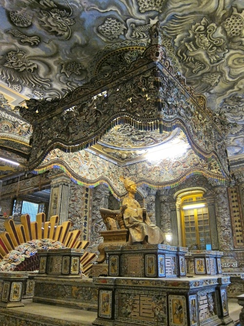 A golden statue of Khai Dinh, former Emperor of Vietnam, with colorful mosaics on the walls and ceiling at Khai Dinh Tomb in Hue, Vietnam