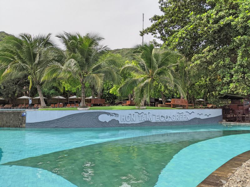 Clean swimming pools with coconut trees surrounding the area at Hon Tam Eco Green area on Hon Tam Island, Vietnam