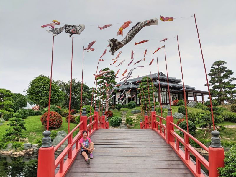 Jackie Szeto, Life Of Doing, sits on the red bridge in VinWonders Nha Trang theme park's Japanese garden area.