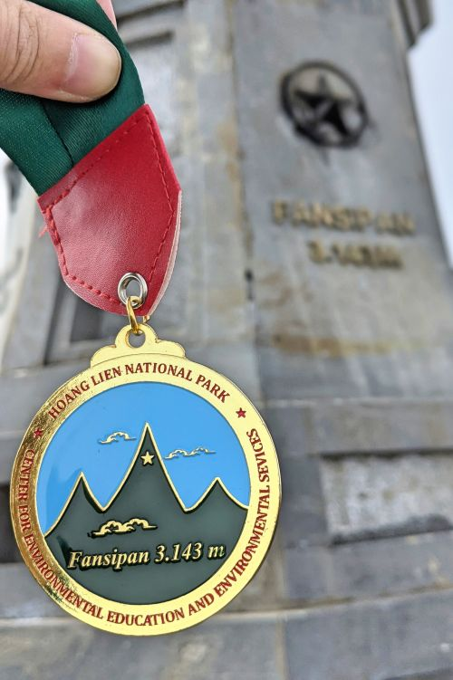 Mount Fansipan hike finisher's medal in front of the Fansipan summit sign in Sapa, Vietnam
