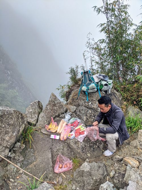 A man prepping sliced tomatoes and cucumbers at a rest stop on the way to Mount Fansipan, Vietnam