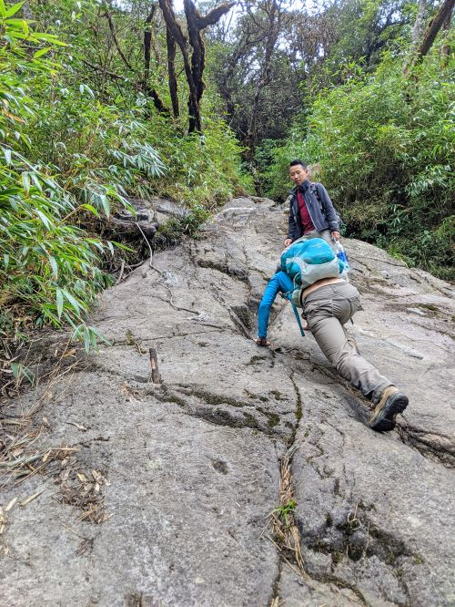 Jackie Szeto, Life Of Doing, and guide scramble up a boulder to reach Fansipan summit in Vietnam