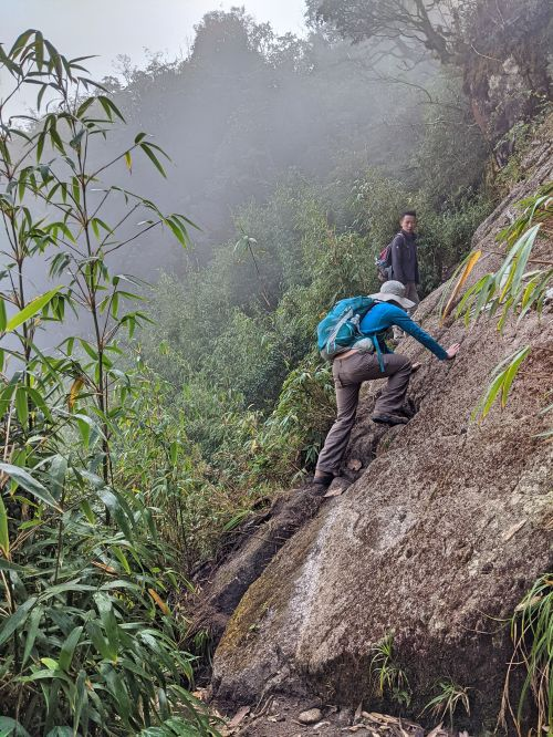 Jackie Szeto, Life Of Doing, and guide climb up a slanted rock on the way to Fansipan summit in Vietnam