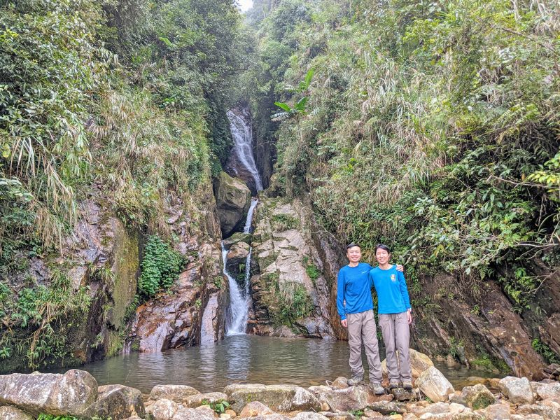 Justin Huynh and Jackie Szeto, Life Of Doing, stand in front of a hidden waterfall along the Sapa 2 day trek from Ta Van village to Giang Ta Chai village.