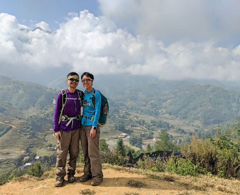 Justin Huynh and Jackie Szeto, Life Of Doing, stand in front of the landscape view of the rice terraces in Sapa, Vietnam