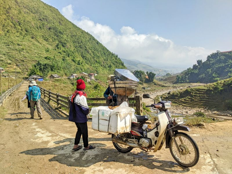 A couple sell steamed buns on a motorbike along the Sapa 2 day trek through Lao Chai village.