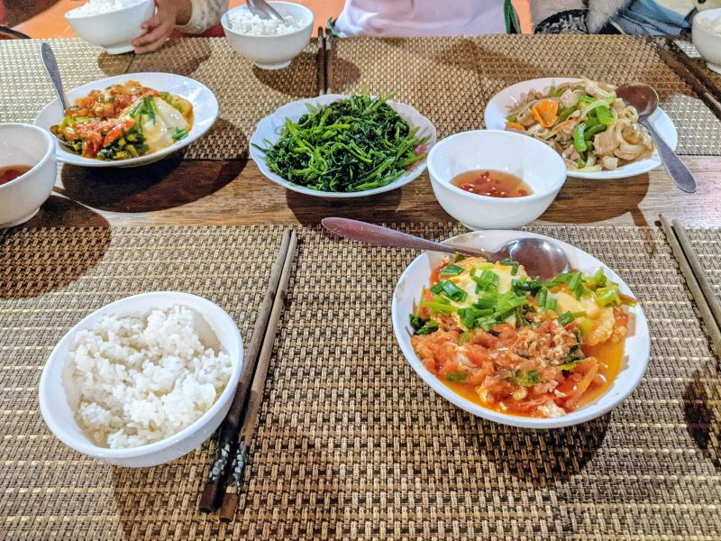 Dinner at Indigo Snail Homestay of duck eggs with tomato, pork with vegetables, morning glory vegetables, and rice