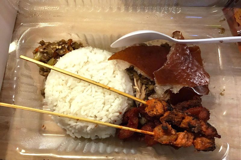 Takeout container of rice with suckling pig and skewers from Karya Rebo