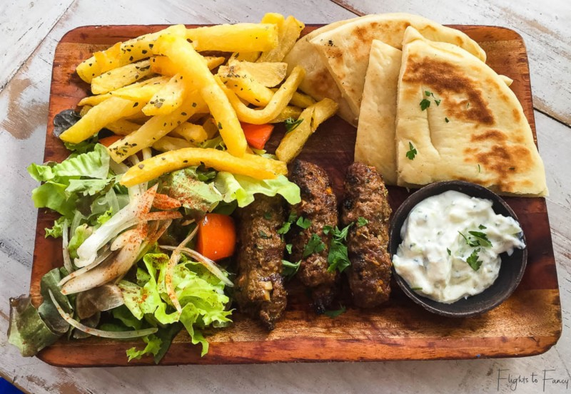 Plate of Greek food with pita bread, fries, grilled meats, and salad