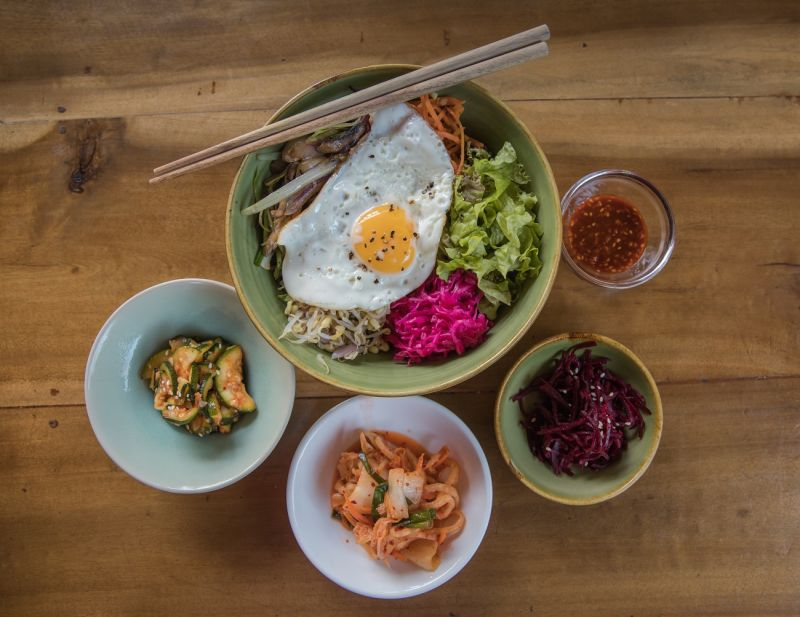Bowl of rice with pickles, fried egg, and vegetables and three small side dishes of kimchi and pickles