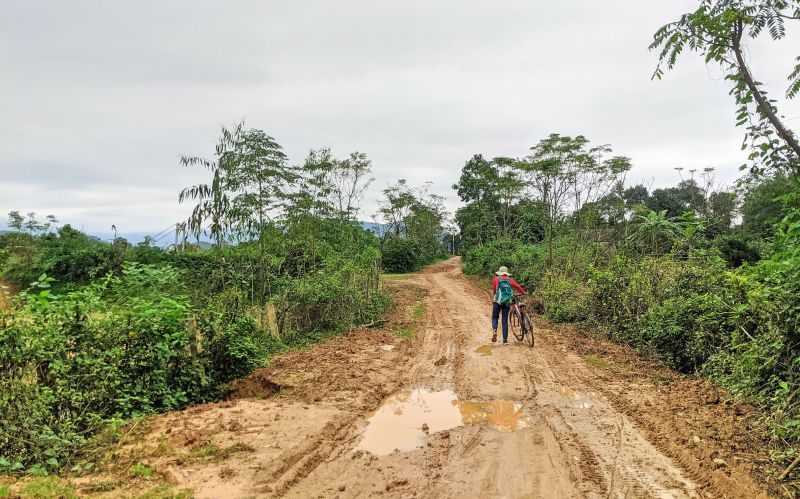 Jackie Szeto, Life Of Doing, walks the bicycle along a muddy path in Bong Lai Valley, Phong Nha, Vietnam