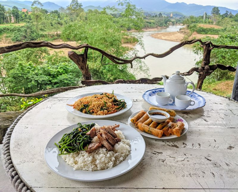 A meal of grilled pork with rice, vegetarian spring rolls, and noodles with vegetables at the original Pub with Cold Beer restaurant in Bong Lai Valley, Phong Nha, Vietnam