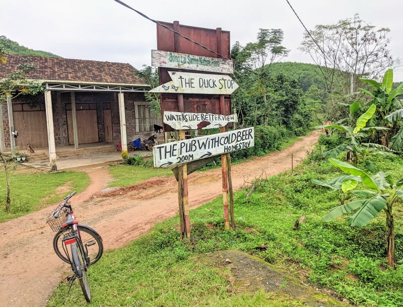 A bicycle stands next to the Pub with Cold Beer and Duck Stop signage in Bong Lai Valley, Phong Nha, Vietnam