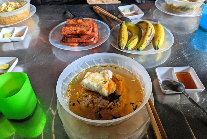 A bowl of instant noodles with fried egg and plates of french toast and banana
