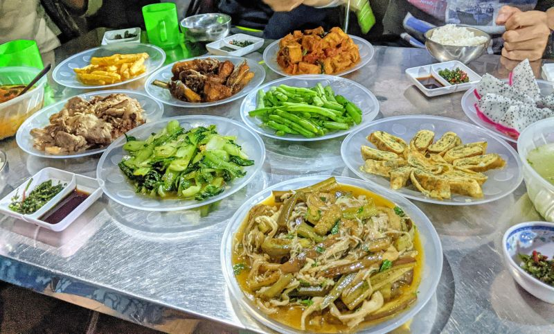 Dinner spread of eggs, mushrooms and eggplant, vegetables, BBQ pork and chicken, french fries on the Hang En Cave tour