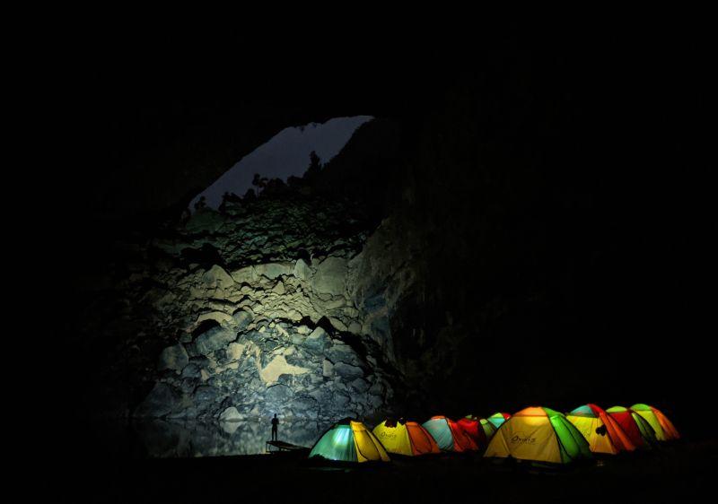 Shadow of a man standing on a pier in front of lit tents in Hang En Cave, Vietnam