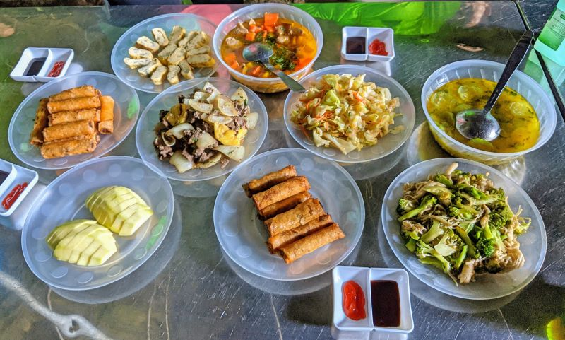 Table of food - eggrolls, broccoli with mushroom, stir-fried cabbage, beef with onions, eggs, and soup