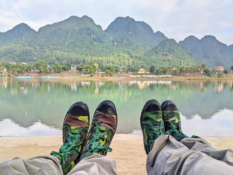 Two pairs of camouflage boots with the river view in the background