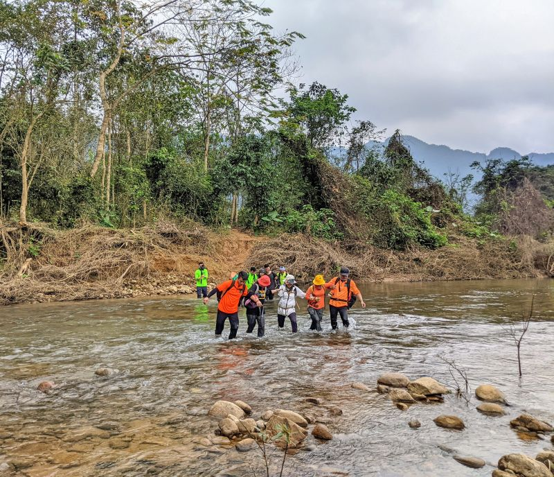 Groups of 3 to 5 people link arms to cross a river during the Hang En cave trekking