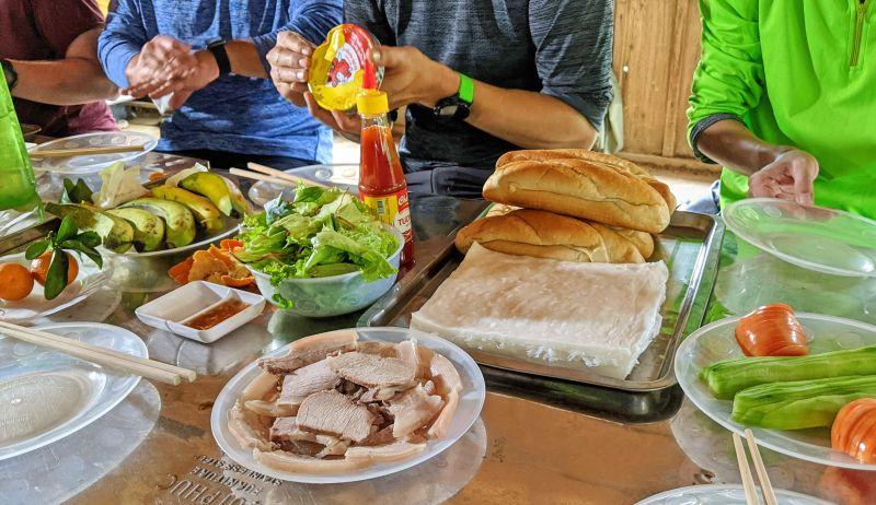 Fresh spring roll ingredients of pork, lettuce, herbs, tomatoes, cucumbers, and baguette