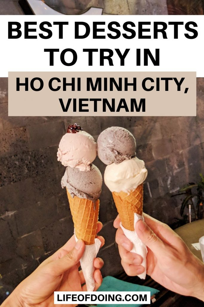 Two hands holding up two ice cream cones with two scoops each in front of a sign at Ho Chi Minh City, Vietnam