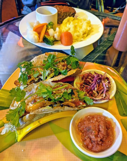 One plate has two tacos with salsa and salad and second plate has meatloaf with vegetables and mashed potatoes at Momma D's Rooftop Lounge in Phong Nha, Vietnam