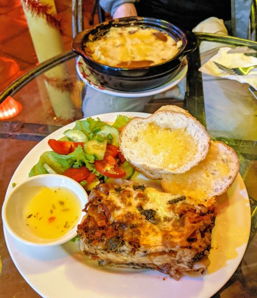One plate has vegetarian lasagna with bread and salad and second plate has shepherd's pie at Momma D's Rooftop and Lounge in Phong Nha, Vietnam