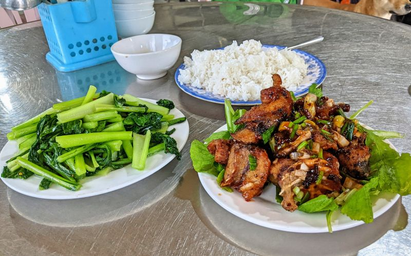 Plate of vegetables and fried fish with rice at Nha Hang Thanh Dat in Phong Nha, Vietnam