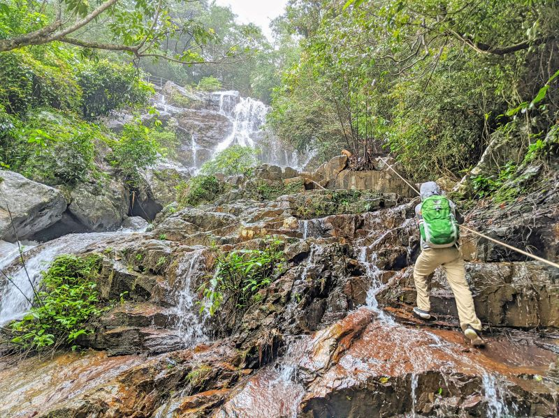 Justin Huynh, Life Of Doing, holds a rope to go up the waterfall at Phong Nha Botanic Garden in Phong Nha, Vietnam