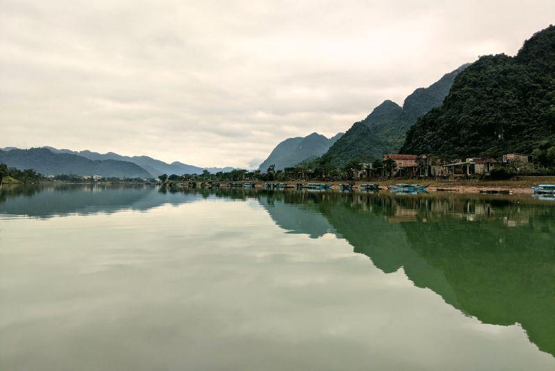 During your Phong Nha itinerary, you'll see boats and houses along the Son River in Phong Nha Ke Bang National Park, Vietnam