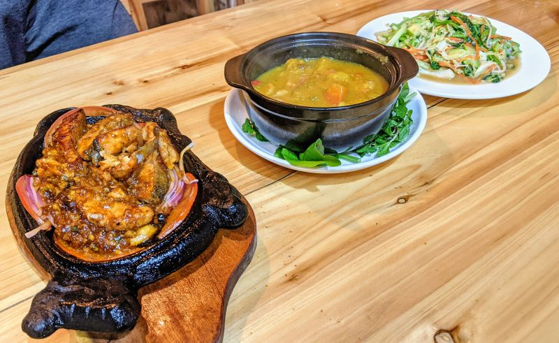 A meal at Good Morning Sapa in Sapa Vietnam - sizzling salmon, yellow curry, and vegetables