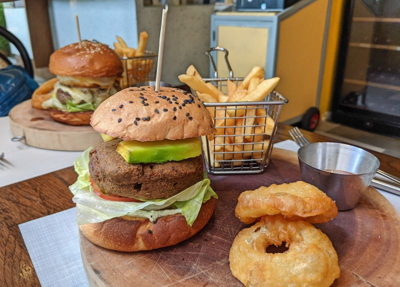 Vegan burger with falafel patty, avocado, tomato, lettuce and fried onion rings and french fries at Cafe Tartine in Ho Chi Minh City, Vietnam