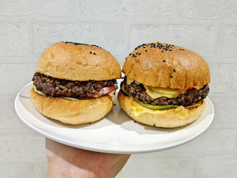 Two vegan burgers with lentils and mushroom patty, lettuce, cashew cheese, tomatoes, and pickles from Happy Cow in Ho Chi Minh City