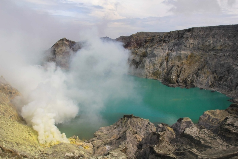 Steam from a turquoise volcanic lake crater at Ijen, Indonesia