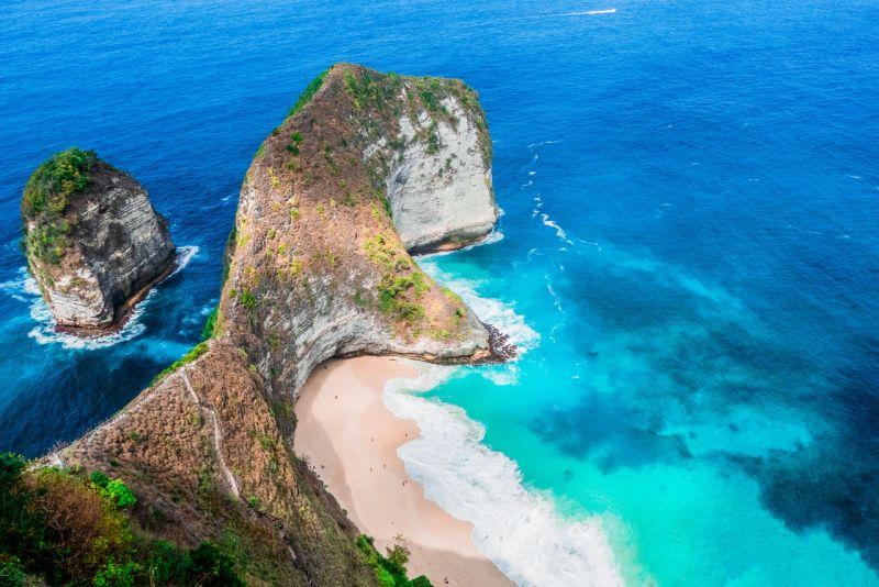 Blue ocean water surrounding the dinosaur backbone looking cliff of Kelingking Beach in Nusa Penida, Indonesia