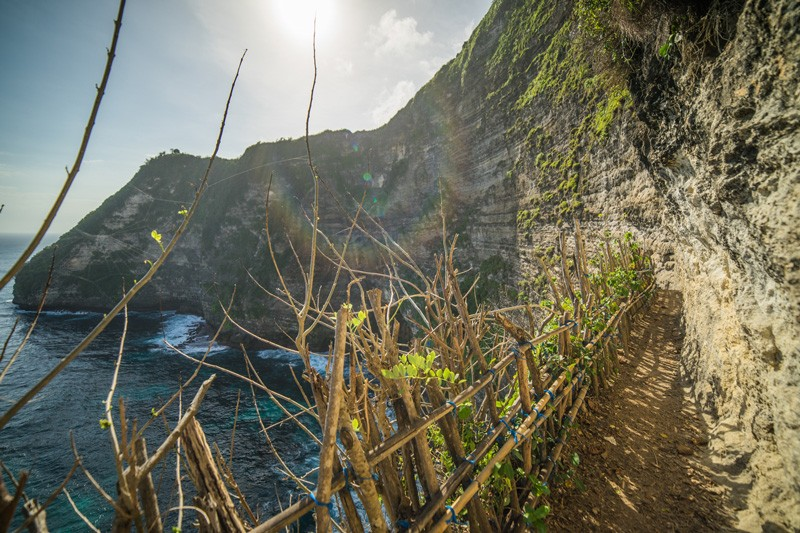 A narrow hiking trail along the cliffside with makeshift rails next to the ocean at Seganing Waterfall in Nusa Penida, Indonesia