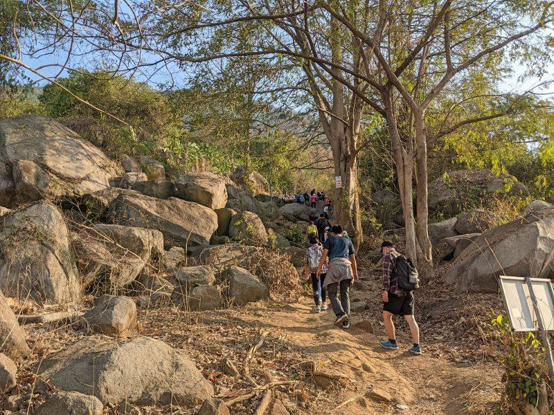 Groups of hikers walk up the dirt path on the Black Virgin Mountain trail in Vietnam