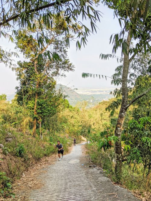 Two hikers going up a steep part of the hiking trail to Cam Mountain (Forbidden Mountain) in An Giang, Vietnam