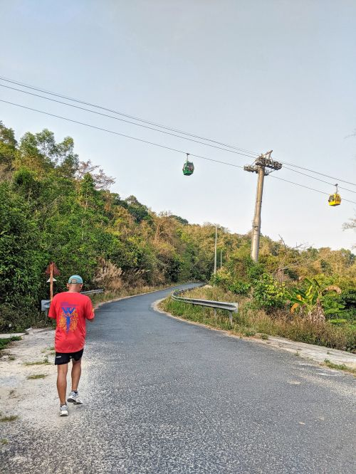 A man in a red shirt walks along the road to go to Forbidden Mountain (Cam Mountain) with cable cars up above in An Giang, Vietnam