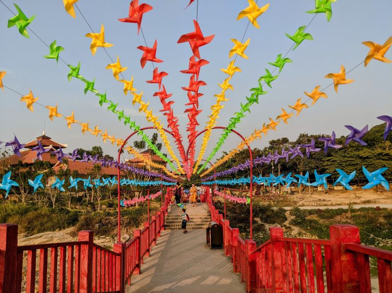 A red bridge with strings of red, yellow, green, orange, blue, and purple pinwheels in the sky