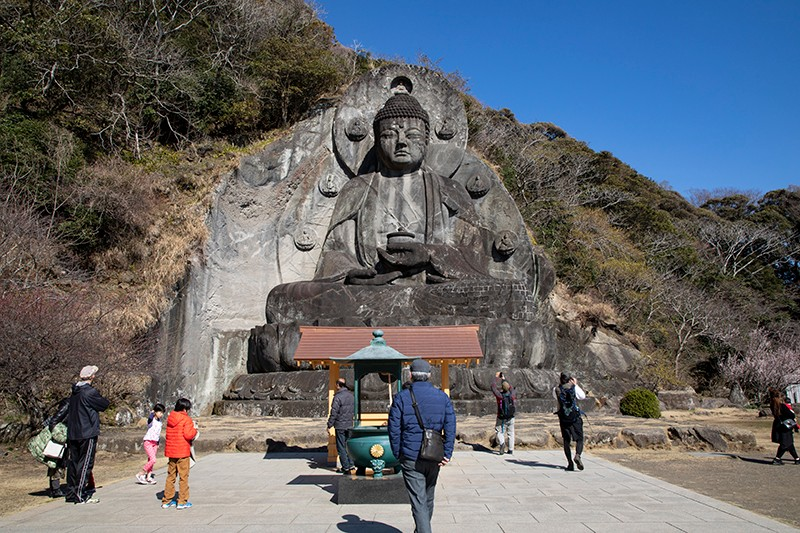 A group of people stands in front of the giant grey Buddha statue on Mount Nokogiri in Japan