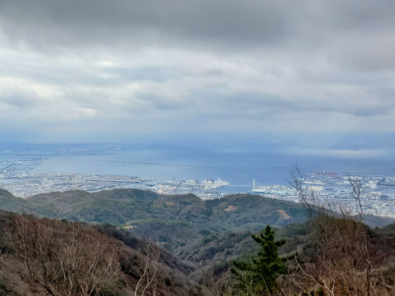 View of the mountains bordering the oceanside off of Mount Rokko in Japan