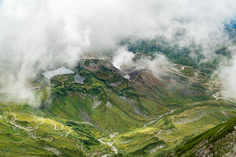 Clouds cover the green mountains and valleys off of Mount Tate summit in Toyama Prefecture